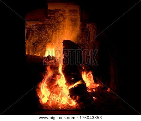 Closeup of burning firewood and embers in fireplace.