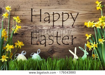Wooden Background With English Text Happy Easter. Easter Decoration Like Easter Eggs And Easter Bunny. Yellow Spring Flower Narcisssus With Grass. Card For Seasons Greetings