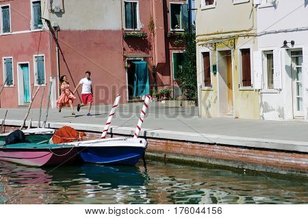 Young couple holding hands walking in Burano Venice Italy Europe