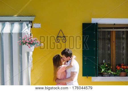 Young couple kissing near a yellow house in Burano island Venice Italy Europe