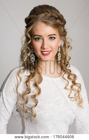 Smiling girl with fashionable hair on a gray background