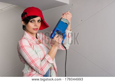 Young pretty woman with an old builder with a drill