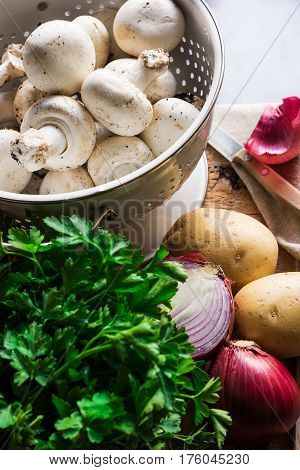 Fresh organic ingredients for preparing healthy vegetarian meal mushrooms in colander potatoes onion parsley knife on kitchen table top view