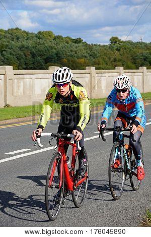 BLITHBURY, UNITED KINGDOM - OCTOBER 2, 2016 - Two cyclists crossing the bridge over Blithfield reservoir Blithbury Staffordshire England UK, October 2, 2016.