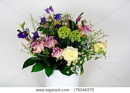 Bouquet of flowers in a white vase against a white background UK.