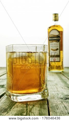 Editorial Photo Of Bushmills Whiskey Glass With Logo And  Blurred Bottle In Background