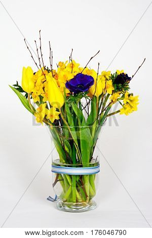 Bouquet of flowers with yellow tulips and daffodils against a white background UK.