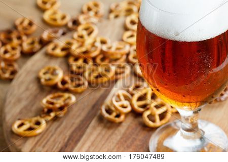 A glass of cold foamy beer with pretzels. Traditional german Oktoberfest snacks and beer on wooden background