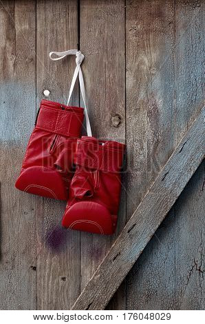 pair of red leather boxing gloves hanging on a nail on a wooden cracked wall