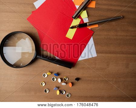 Multicoloured note paper with drawing pins a fountain pen and a magnifying glass on a wooden background