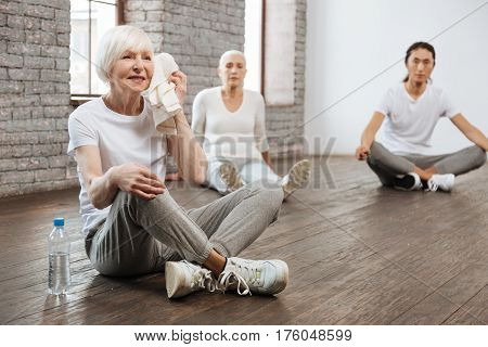 It is your term. Beautiful grey-haired woman wearing fitness clothes holding her hand on the knee while having break