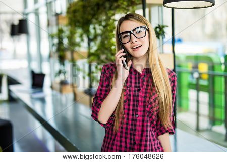 Freelancer Business Woman Talking On The Mobile Phone With Office Buildings In The Background