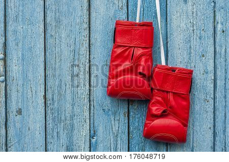 pair of red boxing gloves hanging on a nail on a blue old cracked wall empty space on the left