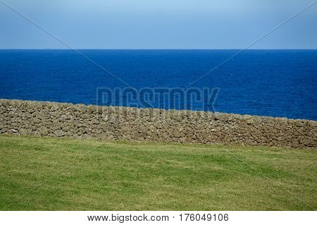 Contrast of green field, volcanic stone wall, ocean and sky