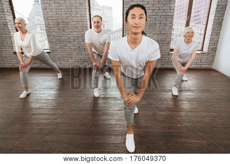 During training. Positive people wearing fitness clothes lunging forward while keeping smile on faces
