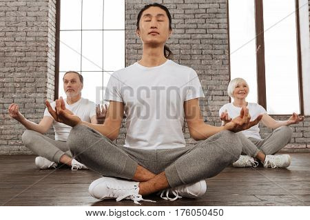 I like yoga. Happy pensioner woman keeping smile on her face sitting behind her tutor while trying to meditate