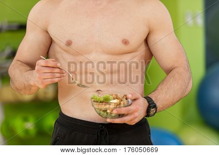 Shaped and healthy body building man holding a fresh salad bowl, shaped abdominal.