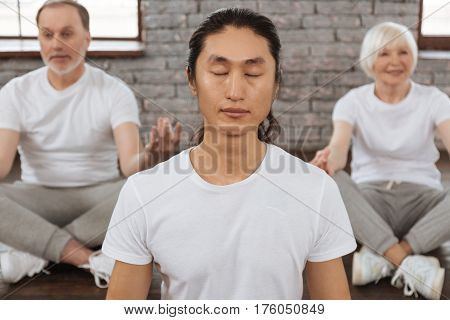 Work with imagination. Young Asian instructor wearing white T-shirt keeping his eyes closed while meditating