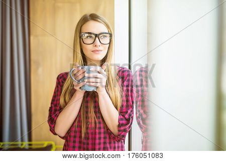 Young Freelance Lady Drinking Coffee In Casual Clothes And Looking Through A Window. Morning.