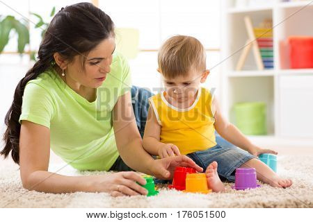 child and his mother or babysitter playing together with educational toys