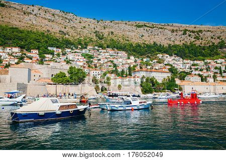 view of the boats at the harbor of the Old port in Dubrovnik and small houses outside the City Walls Croatia