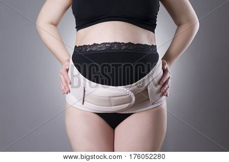 Pregnant woman in black underwear with orthopedic support belt pregnancy bandage studio shot on gray background