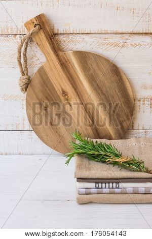 Round wood cutting board stack of linen towels rosemary twig tied with twine on white plank wood background Provence style kitchen interior