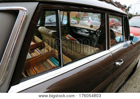 Old car with boxes of books inside parked on a street on a bright day