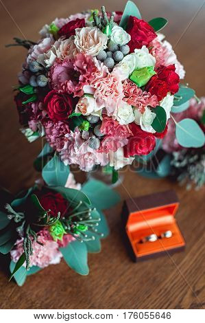Colorful Wedding Bouquet With Roses And Carnations On The Table Next To Bridesmaids Boutonniere And