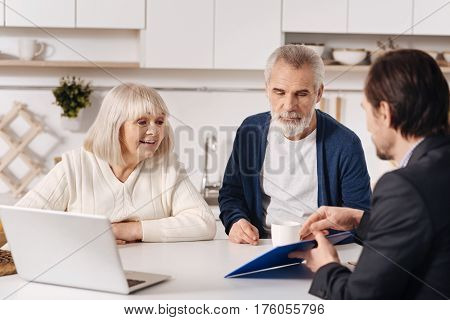 Making important decision. Delighted friendly senior couple sitting at home in front of the laptop and having conversation with realtor while expressing interest