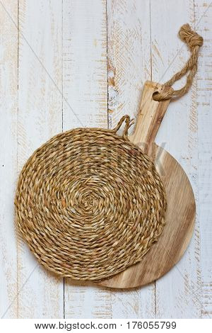 Wood round cutting board and wicker rattan coaster on white plank wood background rustic kitchen interior Provence style minimalistic kinfolk top view