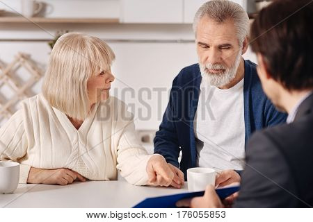 Making a purchase. Decisive involved senior couple sitting at home and having conversation with advisor while expressing interest