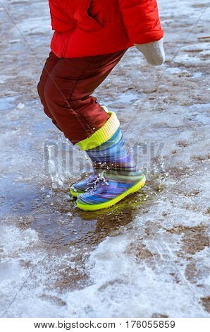 feet in rubber boots jumping in puddle
