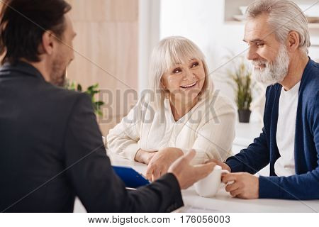 Ready for signing. Delighted upbeat elderly couple sitting at home and having conversation with advisor while expressing positivity and discussing contract