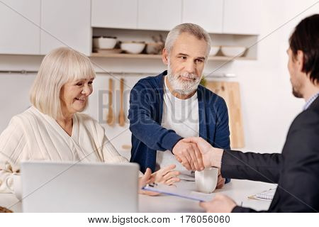 Making deal. Smiling involved elderly couple sitting at home and concluding agreement with real estate agent while expressing positivity and shaking hands