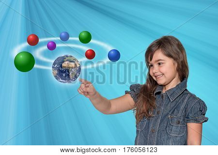 Smiling little girl is touching the Planet Earth and showing another color balls. All is on on the blue gradient background with light rays. Elements of this image furnished by National Aeronautics and Space Administration