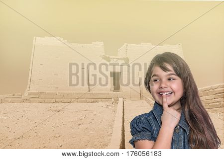 Smiling long haired tanned little girl with her finger over her mouth is standing in front of Temple of Kalabsha in Egypt. Landmark in the background is edited as a vintage photo in sunlight.