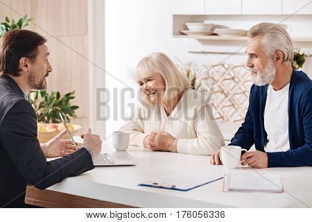 Familiarizing with our services. Charming confident professional real estate agent having conversation with customers and using laptop while expressing positivity