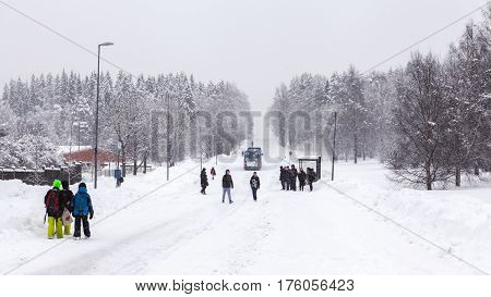 UMEA, SWEDEN ON MARCH 02. View of kids by a bus stop along a snowy road on March 02, 2017 in Umea, Sweden. Buildings, hill and trees in the background. Editorial use.