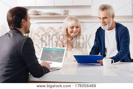 Ready to help. Skillful optimistic sincere finance advisor having conversation with elderly customers and using laptop while expressing positivity