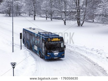UMEA, SWEDEN ON MARCH 02. View of a bus along a snowy road on March 02, 2017 in Umea, Sweden. Trees in the background. Editorial use.