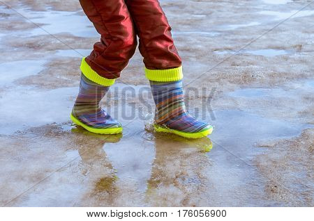 feet in rubber boots in a puddle