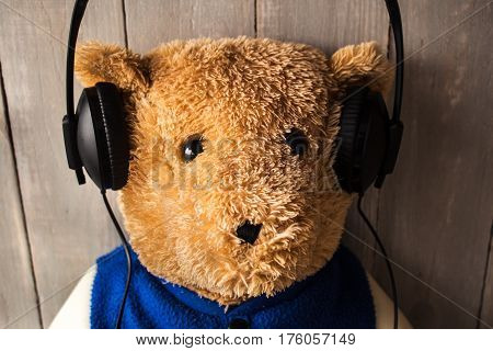 a teddy bear with headphones on wooden background