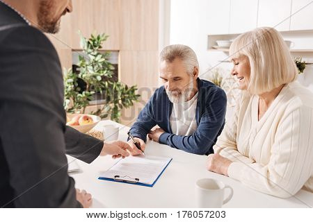 Our mutual decision. Optimistic delighted senior couple sitting at home and having conversation with finance advisor while signing the agreement