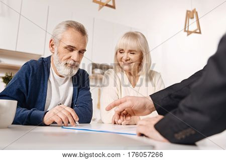 Our important purchase. Decisive happy senior couple sitting at home and having meeting with finance advisor while signing the agreement