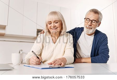 Caring about our grandchildren future. Smiling harmonic positive elderly woman sitting at home next to her husband and expressing happiness while signing documents