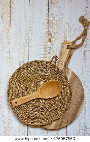 Wood round cutting board and wicker rattan coaster spoon on white plank wood background rustic kitchen interior Provence style minimalistic kinfolk