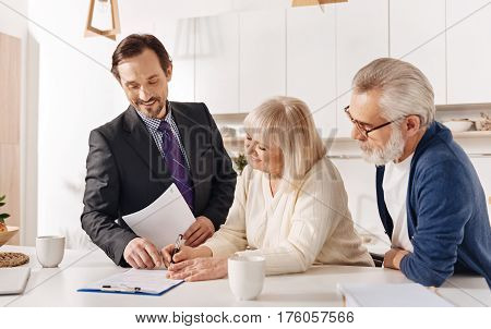 Helping clients to make a choice . Confident proficient skillful real estate agent meeting with aged couple of clients while working and helping customers with choice