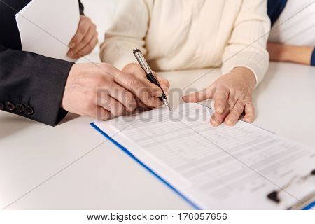 The process of getting the insurance. Aged resolute lonely couple sitting at home and having meeting with social security advisor while signing the insurance document