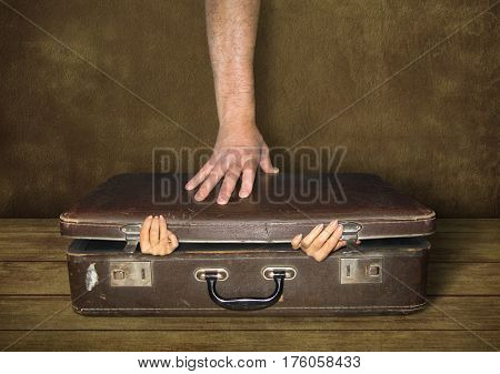 The woman hands are sticking out of old suitcase. And the man hand is pushing on the lid of this suitcase.